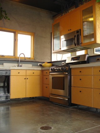 Kitchen with stainless steel appliances complimented with the grey poured concrete floor and walls