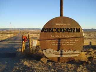 Round, bronze Arcosanti sign with mountains in the background.