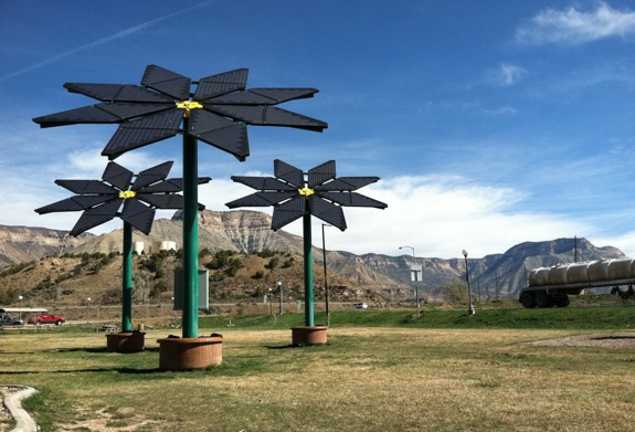 Three flowers made out of solar panels at a rest stop.